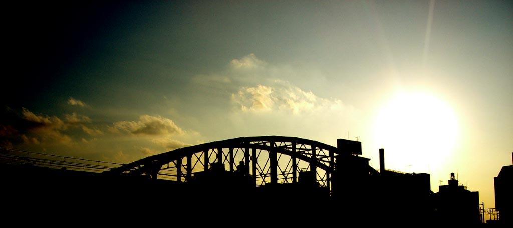 鉄橋のシルエットと太陽