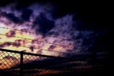 フェンスと有刺鉄線と空