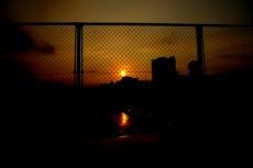 フェンス越しの夕景の写真素材